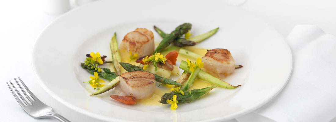 Scallops and brightly coloured flowers and asparagus
